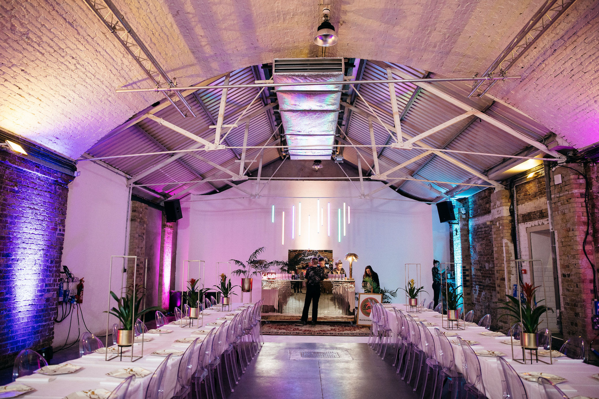 Colourful uplighters, plants and gold decor at Shoreditch Studios wedding