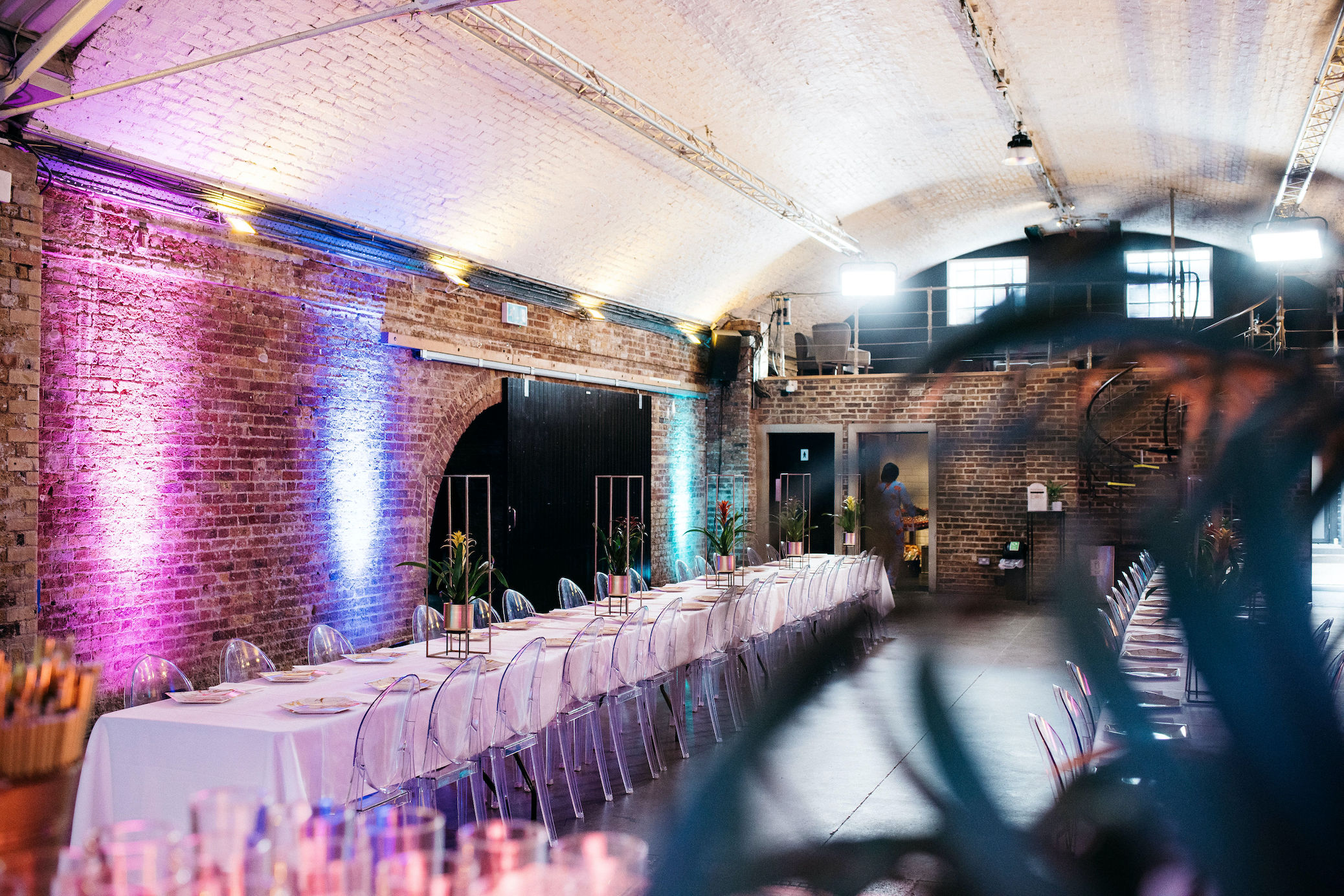 Ghost chairs and banqueting tables, colourful wedding breakfast setup at Shoreditch Studios