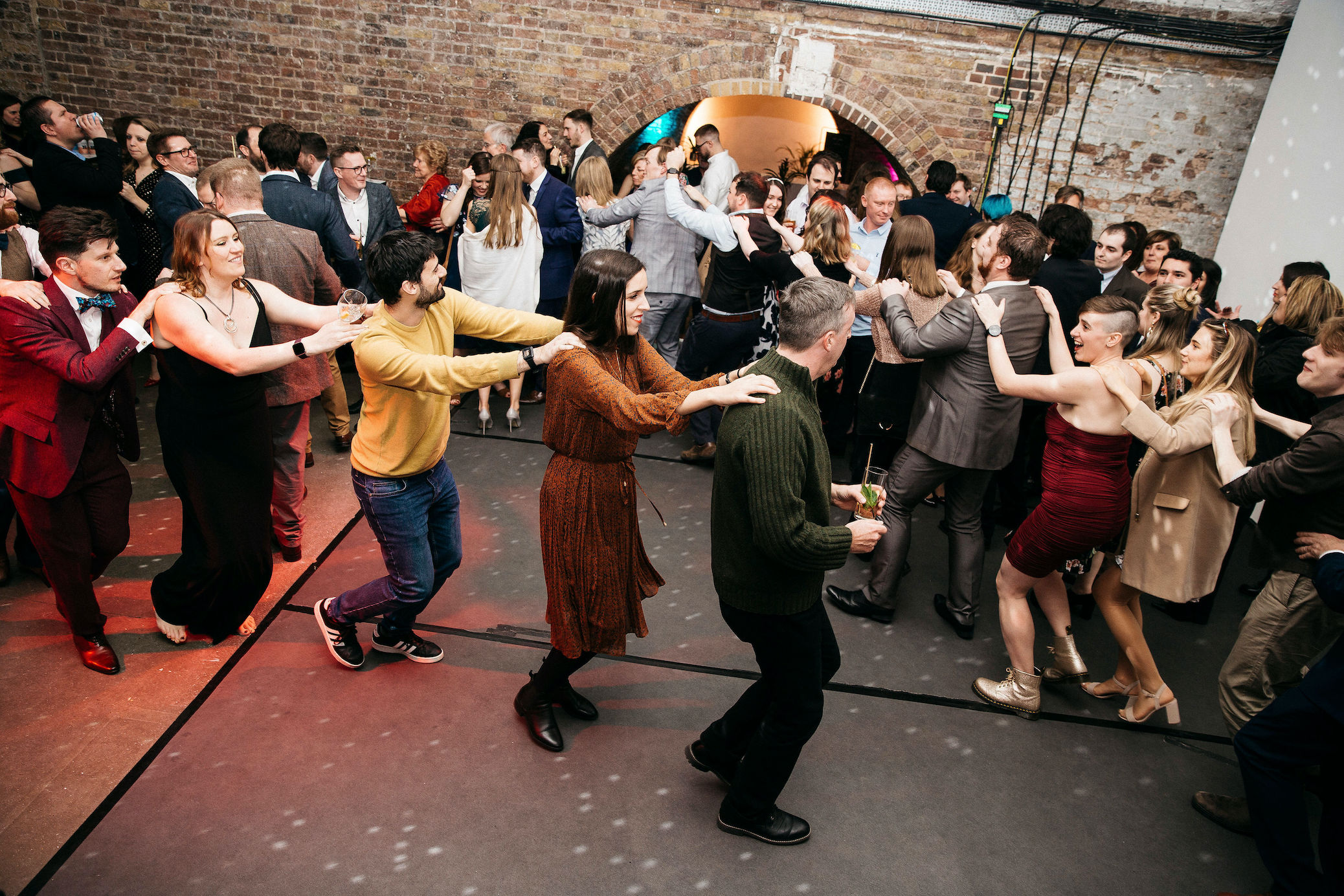 Wedding guests doing the conga line in and out of Shoreditch Studios arches